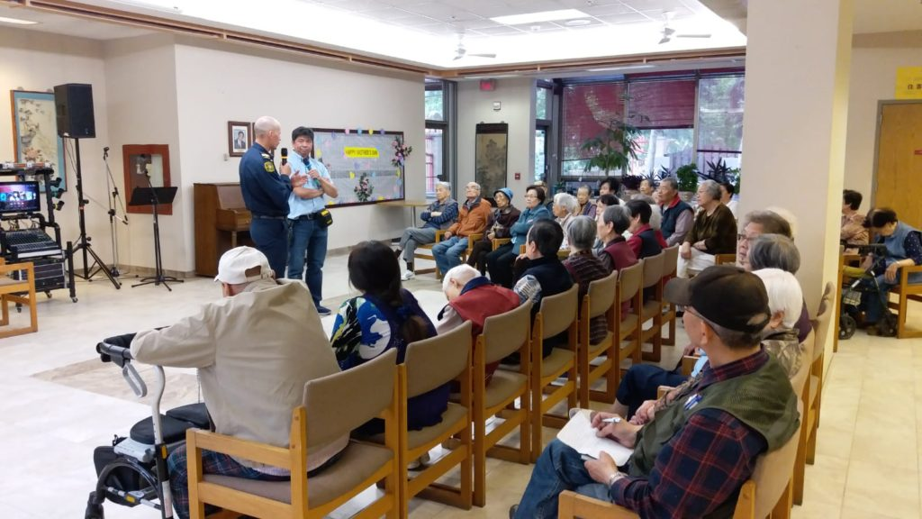 Darrell Wiebe teaching tenants about fire safety and Andy Chan translating.